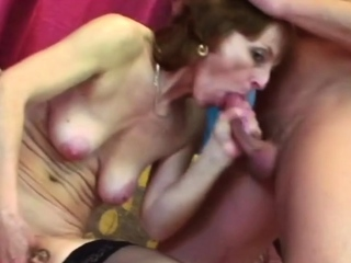 Horny granny is sucking this man's balls while masturbating.